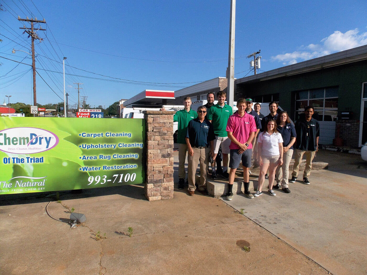 chemdry of greensboro staff in front of building with sign